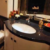 Undermounted sink with top in 'Black Jaq' in Versital. Curved cabinet made to measure by Langleys in White satin.