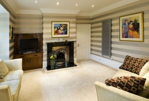 Large lounge area with fitted walnut furniture and railroaded wall paper