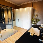 Large designer bathroom with white high gloss bathroom cupboards and central shower