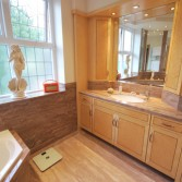 Cream and brown bathroom with fitted bathroom cabinet.