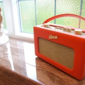 Bright orange Roverts radio on sink cill in brown marble.