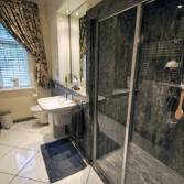 Walk in shower area in 'Gristone' marble panels by Versital.  Features bespoke white satin cabinet and wall hung toilet.