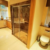 Cream and brown bathroom design with brown marble shower, toilet and sink area.