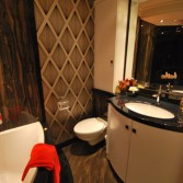 Bathroom with panels in Versital in 'Wenge' and 'Black Jaq'.  Curved bathroom cabinet made to measure