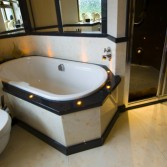 Bathroom featuring bath with light surrounds, panels in 'Autumn Onyx' finish from Versital. All designed by Langleys.
