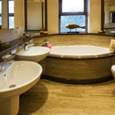 Large shaped bath and double sinks by Villeroy and Boch.  All surfaces by Versital in 'Sandstone' and 'Coco Loco'.