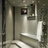 Walk-in shower with flat screen TV, incorporating a built-in seat. Panels by Versital in 'Graphite' and 'Dusk'.