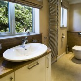 Bathroom designed using Versital in Sandstone with storage cabinet with 3 doors and wall hung toilet.