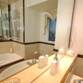 Bathroom with bath and large mirror.  Tops and edging dado by Versital in 'Wenge' and 'Champagne'