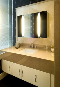 Cream bathroom cabinet with work top and sink. Mirrored lit cabinet.