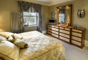 Beautiful bedroom design with real wood, cream bedspread and grey swooping curtains.