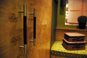Wood wardrobes with black leather effect handle.