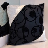 Black and white patterned cushion with swirl pattern and lattice pattern with pearl details.