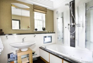 Bathroom with bath, shower and TV in white and oak with V & B Pottery.