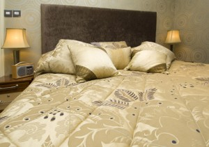 Gold bedspread with diamond pattern and scatter cushions.