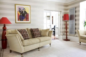 Gold and cream lounge design with 'railroaded' wallpaper and designer radiators.