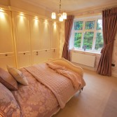 Guest bedroom with cream bedroom furniture and pink bed linen and dusty pink curtains.