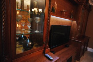 Traditional style lounge furniture in cherry with display cabinets and shelving.