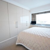 Cream high gloss fitted wardrobes.