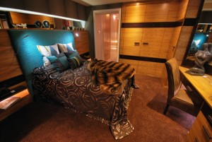 Fitted bedroom furniture with a dark band and light wood with emerald soft furnishings.