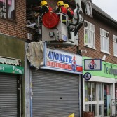 Fire fighters on a cherry picker dig through rubbish to rescue hoarding woman above chicken shop.