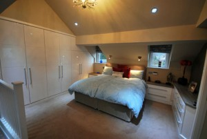 Fitted bedroom furniture in white high gloss in attic room.