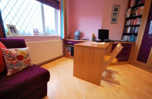 Oak and purple fitted desk and drawers for teem bedroom idea.
