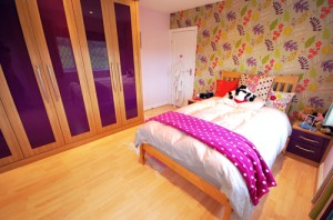 Oak and purple high gloss fitted furniture add a dash of colour to this teen bedroom.