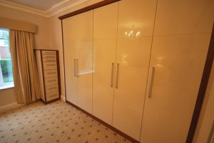Bespoke storage cabinet in cream high gloss with cherry wood surround.