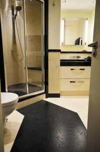 Black and white bathroom with custom floor slab pathway