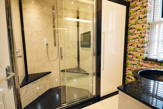 Large double seated black and white shower and white high gloss cabinet.