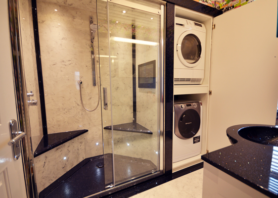 Black and white style bathroom with double seats and built in washer and dryer.