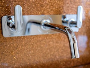 Chrome wall mounted tap and bronze sparkly panel