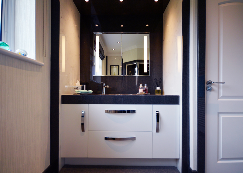 White bathroom cabinet with black granite