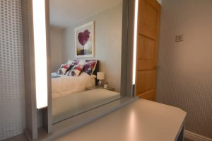 Bespoke fitted bedroom with custom dressing table and LED lighting